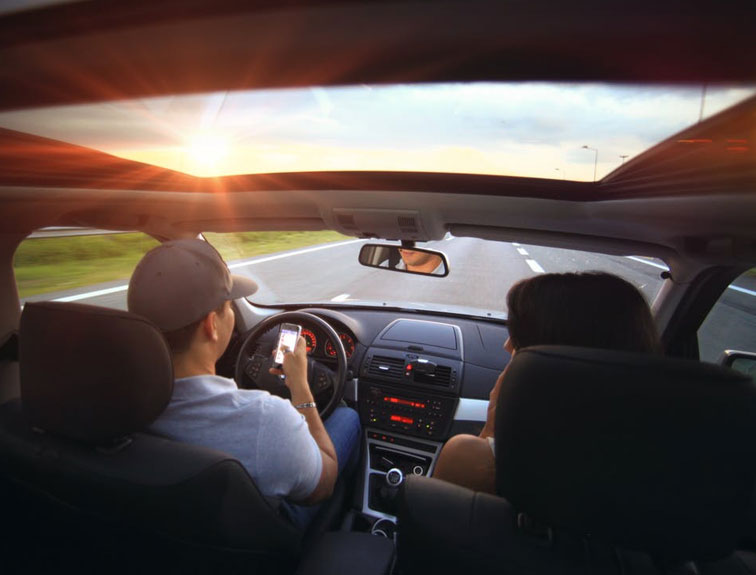 Pictured are two people riding in a vehicle, while the driver is looking at his phone.