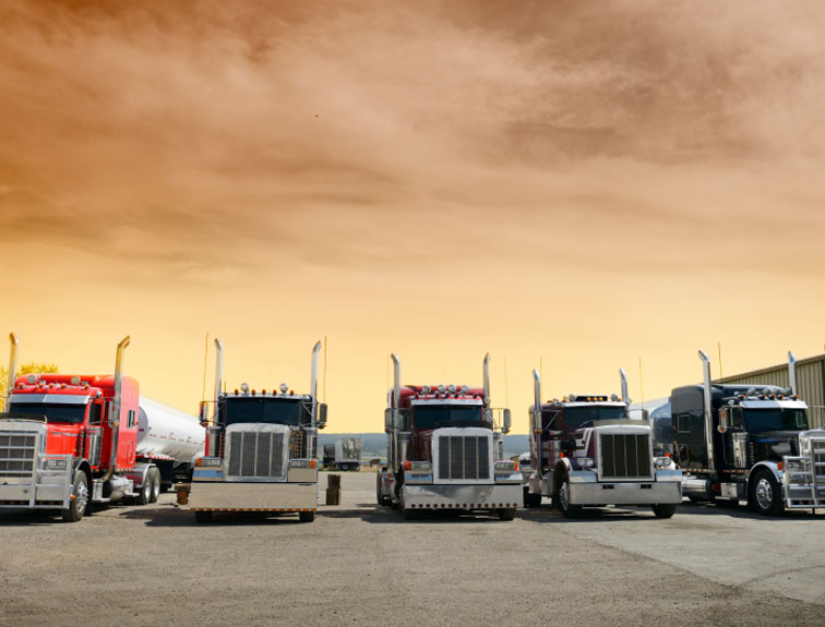 Pictured are 5 semi trucks lines up at a truck stop with a yellow-orange sky.