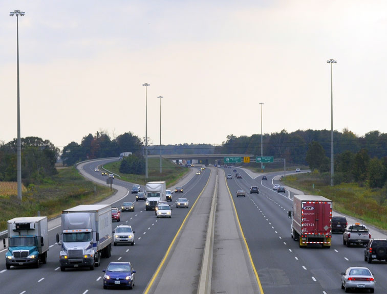 Pictured are trucks and cars traveling on a highway.