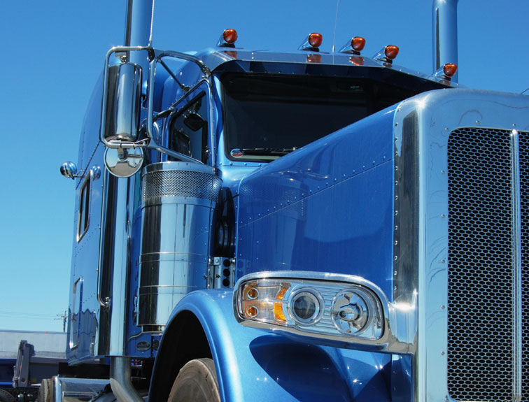 Pictured is the cab of a blue truck on a blue, clear day.