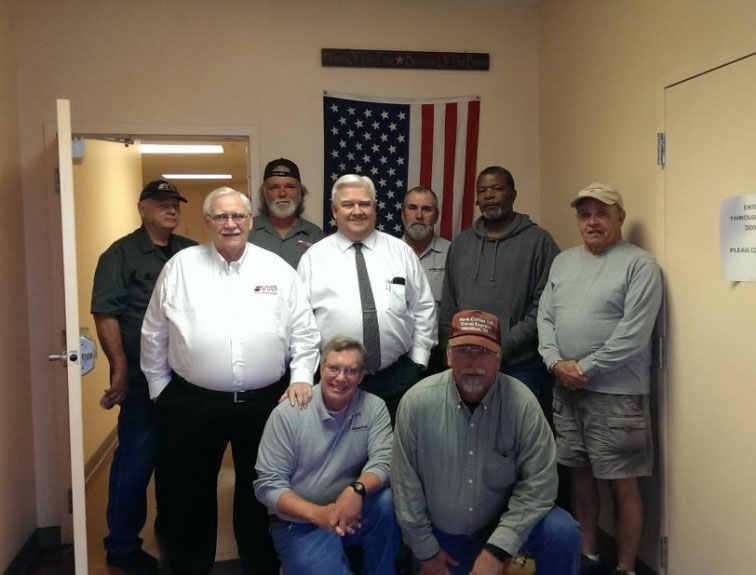 Pictured are the 9 Napier staff who are veterans standing in front of an American flag.
