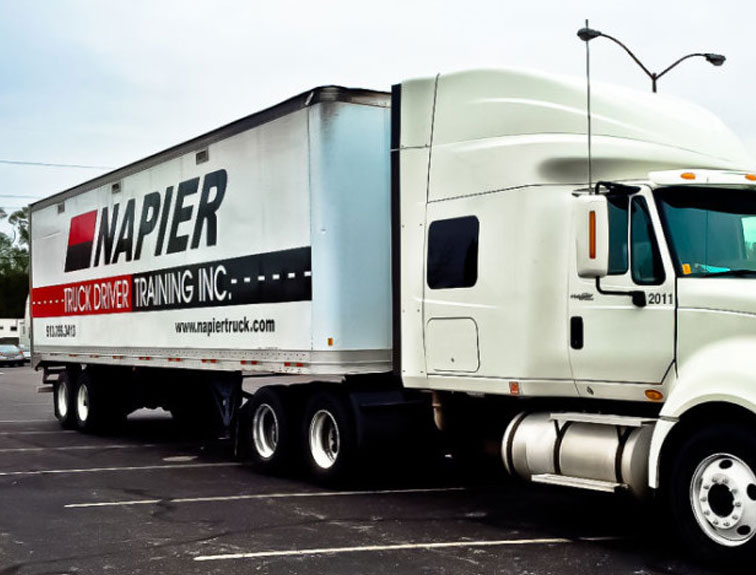 Pictured is a white Napier truck parked in the CDL training parking lot.