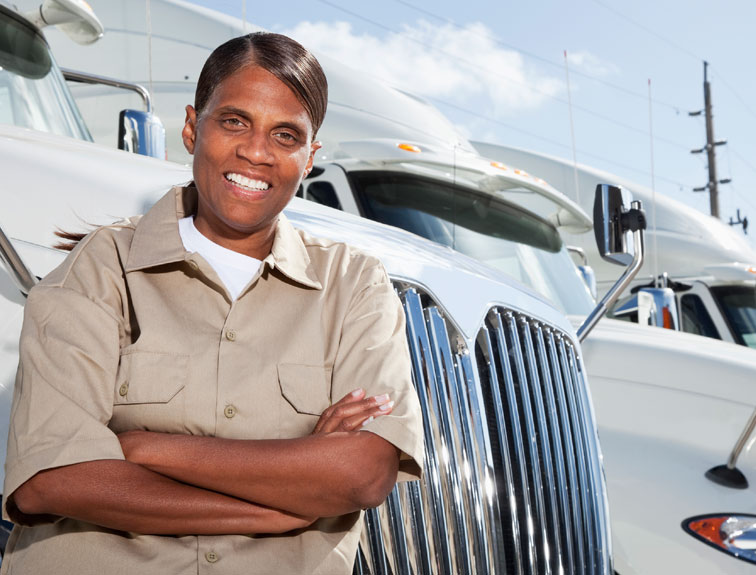 Pictured is a woman standing in front of a row of white trucks, representing women in trucking.