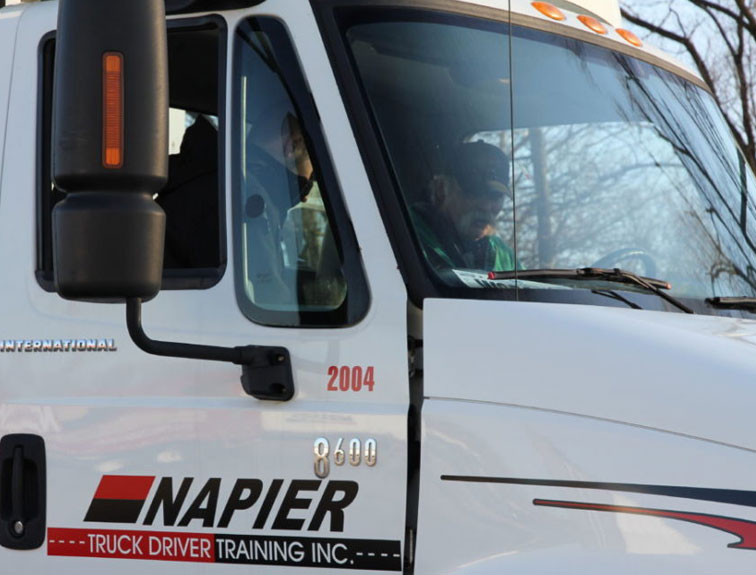 Pictured are a truck driving instructor and a student sitting in the cab of a Napier truck discussing essential electronics for truckers.
