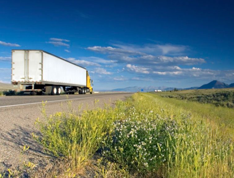 Pictured is a truck driving on an open road.