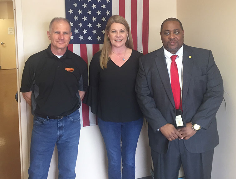 image of representatives from Schneider National, Napier Truck Driver Training, and Community Action Agency standing in front of an American Flag in the background