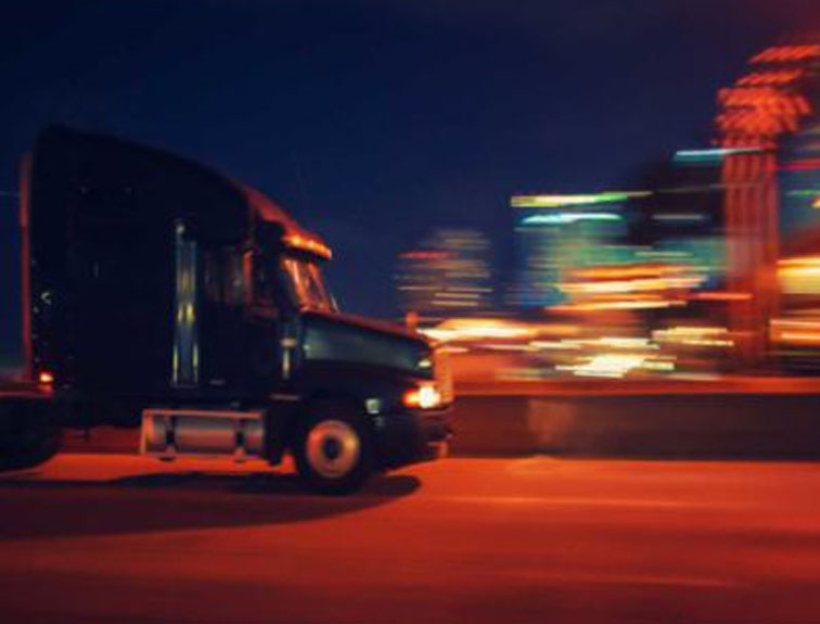 Pictured is a Semi Truck Driving At Night