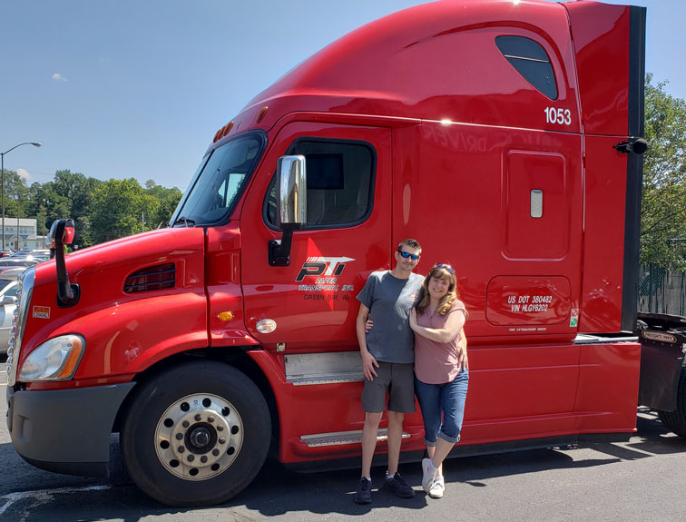 Two people posing in front of a semi