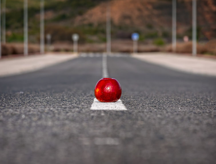 Red apple in the middle of the road.
