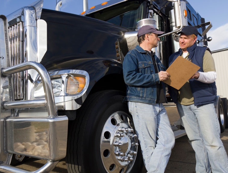 Two men talking with clipboard and a semi in the background