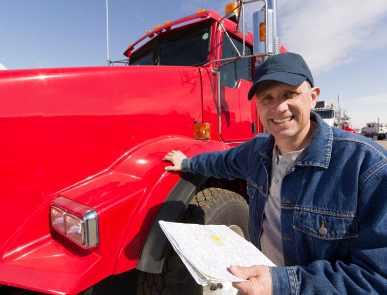 Man in a jean jacket with clipboard and hand on a red semi