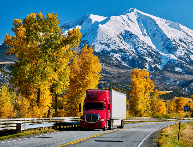 Red truck driving through mountains